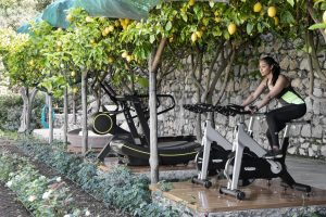 Young woman enjoing the fittnes area under the lemon trees at Hotel Il San Pietro di Positano,Relais & Chateaux on the Amalfi coast