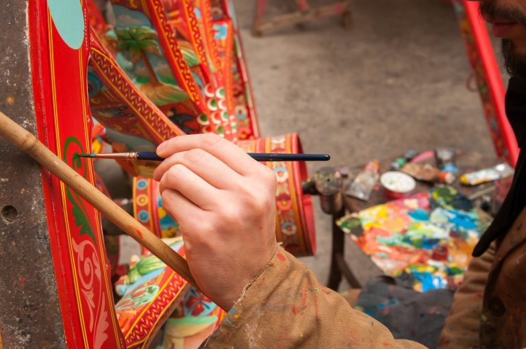Hand of a sicilian cart painter while finishing some colored details of a wheel: workshop of the sicilian folkloric craftsmanship Rosso Cinabro, Ragusa Ibla
