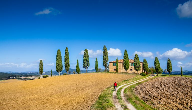 Scenic Tuscany landscape with farmhouse and cyclist on a sunny day, Italy
