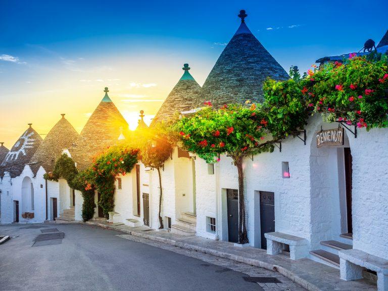 Traditional Trulli houses in Alberobello village, illuminated by sunrise. Apulia region - Italy.