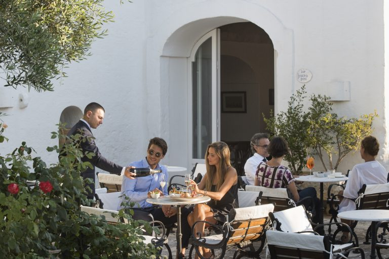 Young couple having a drink at the bar of Masseria Il Melograno in Monopoli