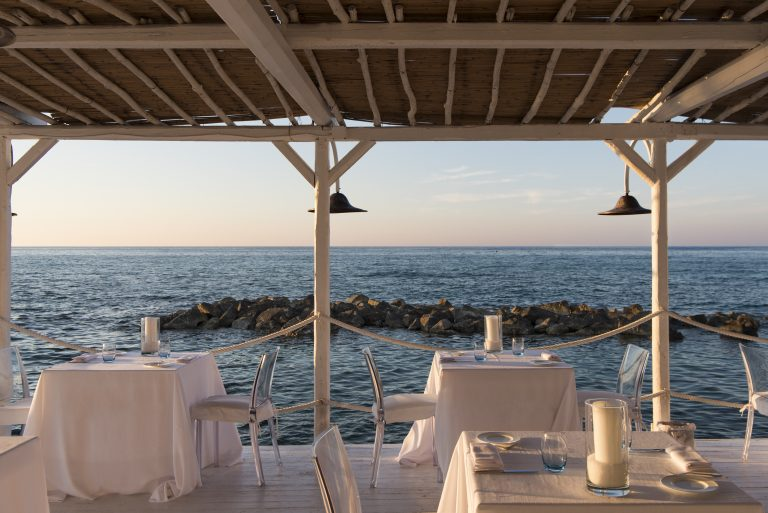 Set tables for dinner in the terrace of restaurant sale Blu at La Peschiera in Monopoli