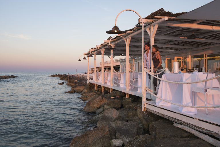 Young couple enjoing the sunset in the terrace of restaurant sale Blu at La Peschiera in Monopoli