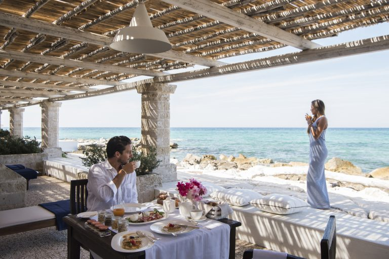 Young couple enjoing breakfast in the  terrace of bedroom110 at La Peschiera in Monopoli