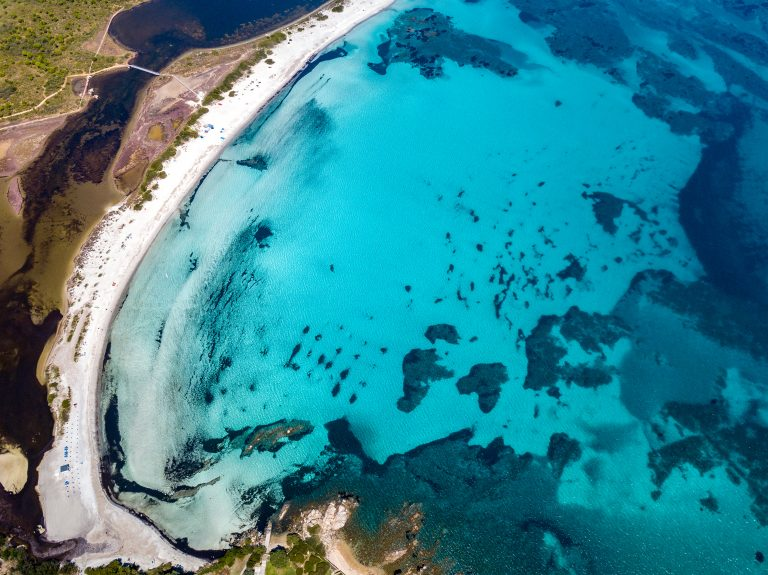 BEAUTIFUL AERIAL VIEW OF THE BEACH OF LU IMPOSTU WITH THE BACKGROUND OF THE ISLAND OF TAVOLARA